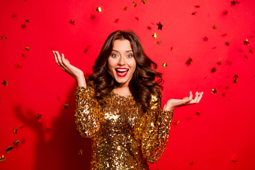 Woman smiling with raised hands with confetti falling